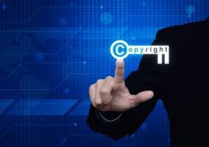 Businessman pressing copyright key icon over digital world map